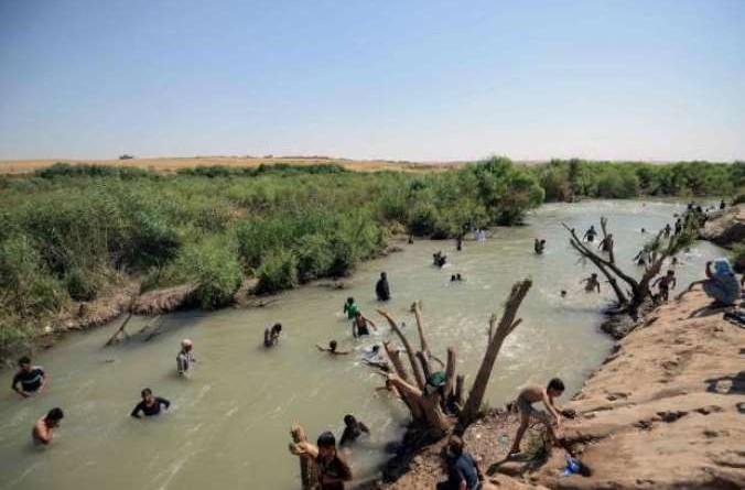بالصور: السباحة في نهر الخازر المتنفس الوحيد للشبان النازحين من الموصل